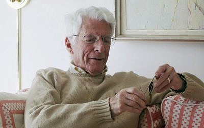 93-year-old Edwin Shifrin at home in Clayton, Missouri, in February 2016, looking at a prisoner-of-war medal he just received for his World War II military service. The award was expedited by US Sen. Claire McCaskill of Missouri after she was approached by Shifrin's family about his clever escape from a Nazi prison camp. (Marianne Shifrin/Dan Shifrin via AP)