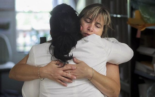 Nina Blakeman, right, of the Palm Beach Zoo receives a hug inside the zoo office after zookeeper Stacey Konwiser, Friday, April 15, 2016 in West Palm Beach, Fla. (Damon Higgins/Palm Beach Post via AP)