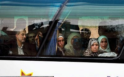 In this April 14, 2016 image, Syrians look through a window after they loaded their belongings onto a bus in the town of Palmyra in the central Homs province, Syria. (AP Photo/Hassan Ammar)
