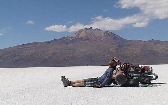 """Roei """"Jinji"""" Sadan rests while crossing the desert in Bolivia during his round-the-world bike trip from 2007 to 2011. (Courtesy Roei Sadan)"""