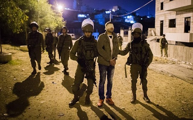 Illustrative: IDF soldiers arrest a Palestinian man in the Dheisheh refugee camp, near the West Bank city of Bethlehem, on December 8, 2015. (Nati Shohat/Flash90)