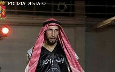 In an image released April 28, 2016, by Italian police, kickboxer Abderrahim Moutaharrik is seen wearing boxing gloves, shorts, a keffiyeh and a black shirt styled after the IS flag. (Italian Police)
