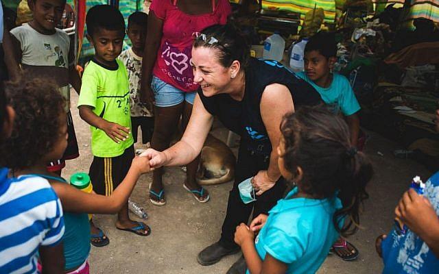 An IsraAID volunteer with Ecuadorean children in Canoa, Ecuador, on April 23 2016. (IsraAID)
