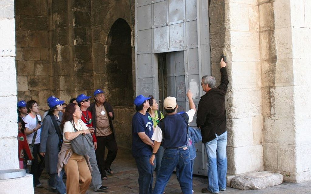 A tour group examines the mezuzah at the Old City entrance. (Shmuel Bar-Am)