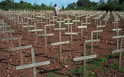 A young Rwandan girl walks through Nyaza cemetery outside Kigali, Rwanda, on Monday November 25, 1996, where thousands of victims of the 1994 genocide are buried (AP Photo/Ricardo Mazalan)