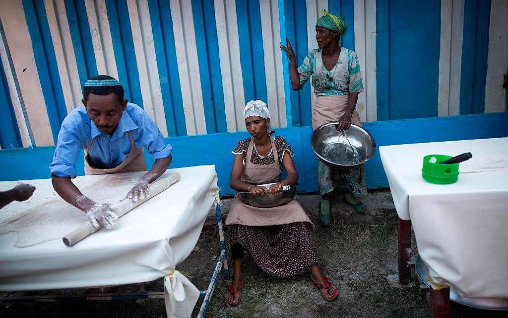 The men of Gondar's Jewish community mix the flour and water in eight minutes, before handing it off to the women who tend the fires.(Miriam Alster/Flash90)