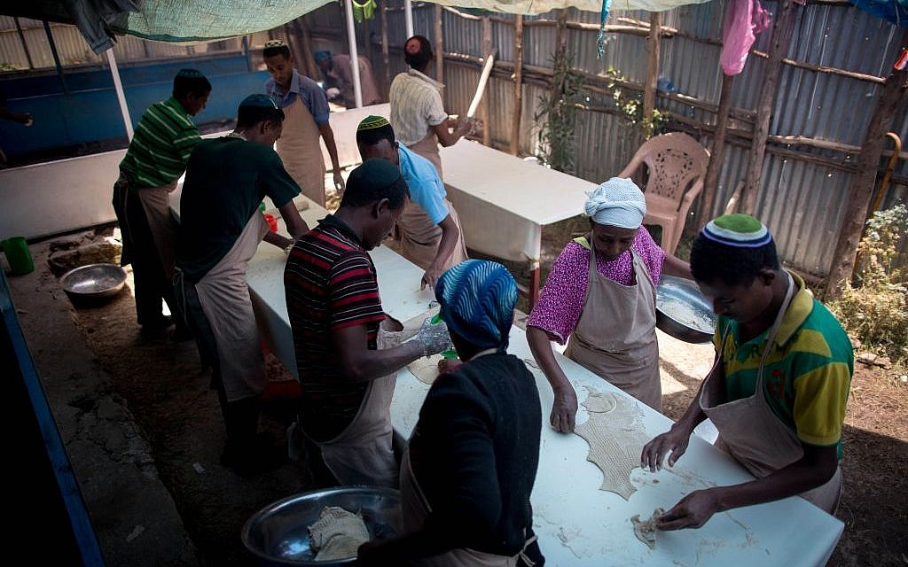 The men of Gondar's Jewish community use a large cookie cutter to cut the matzah into large circles on April 20, 2016. (Miriam Alster/Flash90)