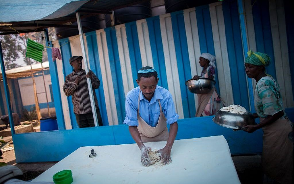 In between rounds of matzah preparation, the men of Gondar's Jewish community wipe off the tables to ensure no drop of water remains, on April 20, 2016. (Miriam Alster/Flash90)