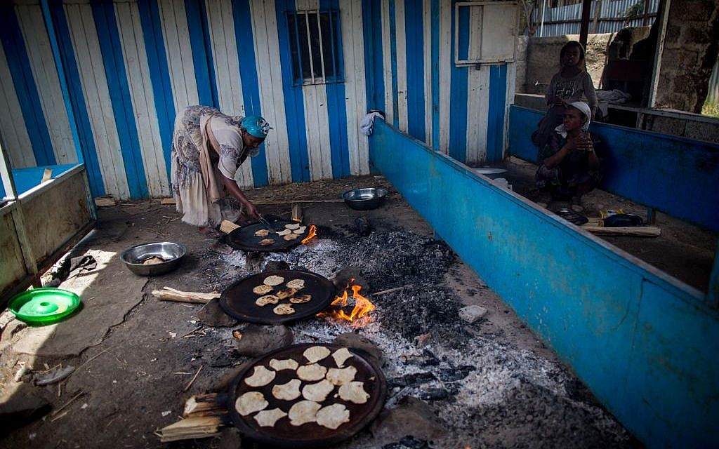 Women of Gondar's Jewish community prepare matzah before Passover on April 20, 2016. The matzah must stay on the fire for less than 10 minutes, so it is cooked in less than 18 minutes and is kosher for Passover. (Miriam Alster/Flash90)