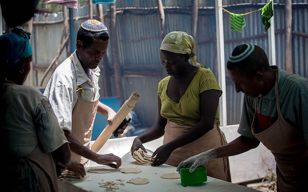 Illustrative: Members of the Gondar, Ethiopia, Jewish community prepare matzah before Passover on April 20, 2016. Women collect cut matzah dough to bring to the stove. (Miriam Alster/Flash90)