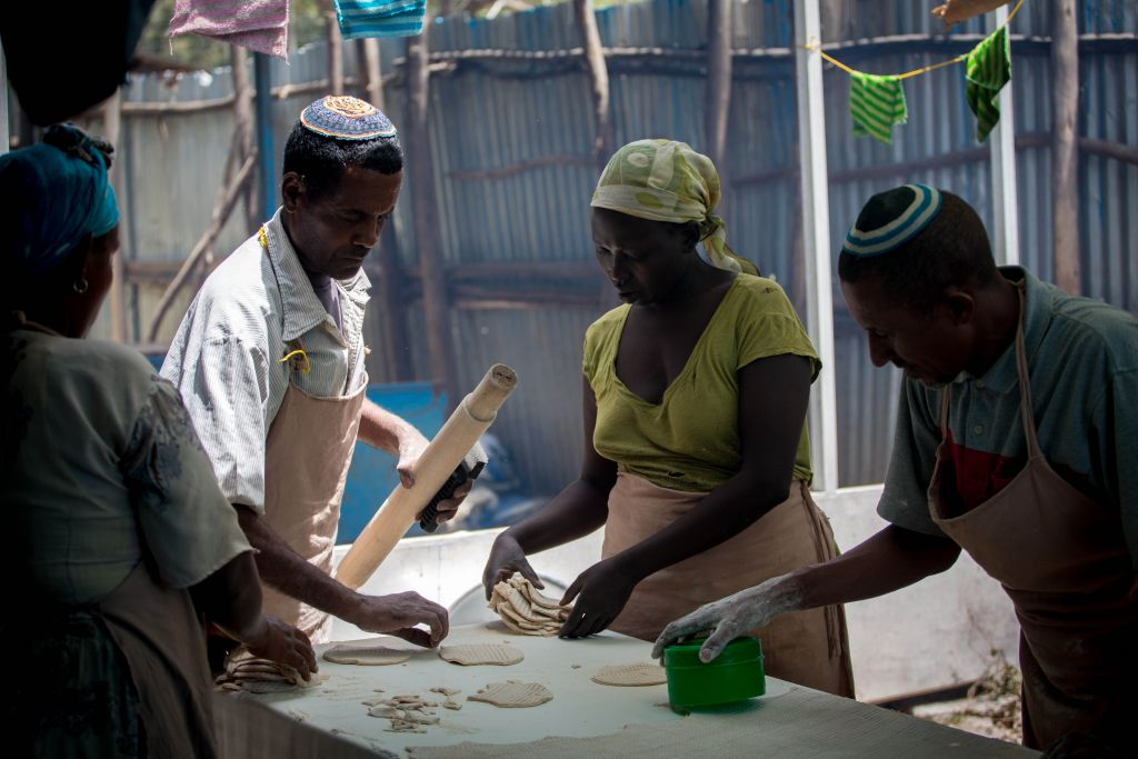 Members of Gondar's Jewish community prepare matzah before Passover on April 20, 2016. Women collect cut matzah dough to bring to the stove. (Miriam Alster/Flash90)