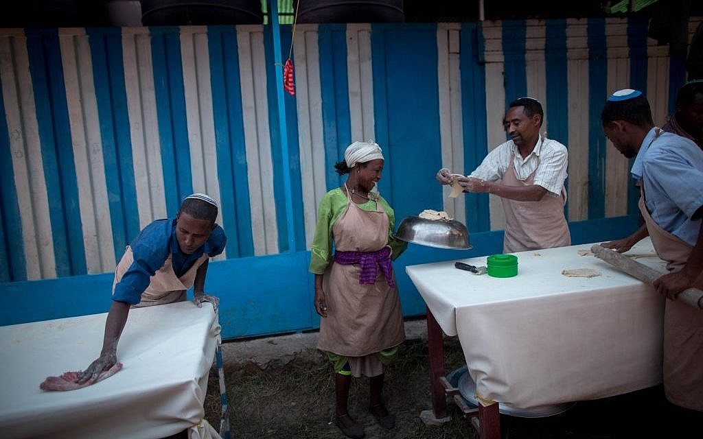 Members of Gondar's Jewish community prepare matzah before Passover on April 20, 2016. The matzah dough hand-off has to be done quickly and efficiently so that the matzah can be cooked in less than 18 minutes. (Miriam Alster/Flash90)