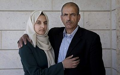 Ismail al-Wawi, 54, right, and Ghayda al-Wawi, 17, the father and the sister of a 12-year-old Palestinian girl imprisoned by Israel for allegedly attempting to carry out a stabbing attack in a West Bank settlement, pose for a photo at the family house in the West Bank village of Halhul, Hebron, April 11, 2016. (AP/Nasser Nasser)