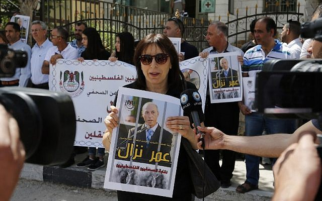 Palestinian journalists hold placards and banners during a demonstration on April 24, 2016, outside the Red Cross offices in the West Bank city of Ramallah, in support of their colleague, Omar Nazzal, who was detained the previous day by Israeli forces. (AFP Photo/Abbas Momani)