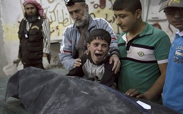 A Syrian boy is comforted as he cries next to the body of a relative who died in a reported airstrike on April 27, 2016 in the rebel-held neighborhood of al-Soukour in the northern city of Aleppo. (AFP PHOTO / KARAM AL-MASRI)