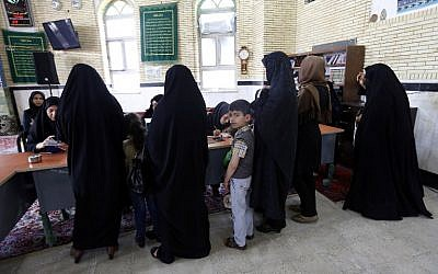 An Iranian young boy looks on as women arrive to cast their vote in the second round of parliamentary elections at a polling station in the town of Robat Karim, some 40 kms southwest of the capital Tehran, April 29, 2016. (AFP/ATTA KENARE)