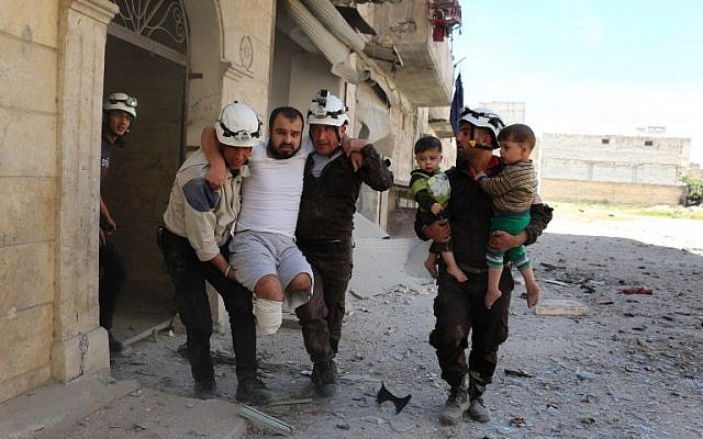 Syrian civil defense volunteers evacuate a man and children from a residential building following a reported air strike on the rebel-held eastern neighborhood of Bab al-Nayrab in Syria's Aleppo, on April 29, 2016. (AFP/Ameer Alhalbi)