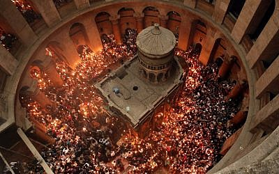 Christian Orthodox worshippers hold up candles lit from the 'Holy Fire' as thousands gather in the Church of the Holy Sepulchre in Jerusalem's Old City, on April 30, 2016, during the Orthodox Easter ceremonies.(AFP PHOTO / THOMAS COEX)