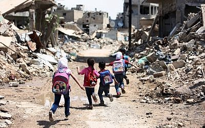 Syrian schoolchildren run past heavily damaged buildings in the rebel-held are of Jobar, on the eastern outskirts of the capital Damascus, April 30, 2016. (AFP Photo/Amer Almohibany)