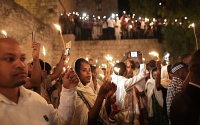 "Ethiopian Christian pilgrims hold candles during an Ethiopian Orthodox ceremony of the ""Holy Fire"" at the Dir Al-Sultan Church held on the roof of the Holy Sepulcher in Jerusalem's Old City on April 30, 2016.(AFP PHOTO / MENAHEM KAHANA)"