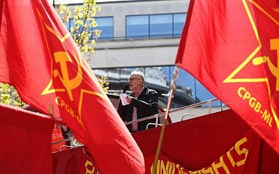 Britain's opposition Labour Party leader Jeremy Corbyn gives a speech from the top of a double-decker bus as Communist Party of Great Britain (Marxist-Leninist) flags fly at a May Day rally in London on May 1, 2016. (AFP / JUSTIN TALLIS)