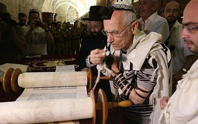 Jewish Holocaust survivors wear the tefilin, or phylacteries, and the tallit prayer shawl as they read from the Torah scrolls during their bar mitzvah ceremony, normally done at the age of 13, on May 2, 2016, at the Western Wall in Jerusalem's Old City. (AFP Photo/Menahem Kahana)