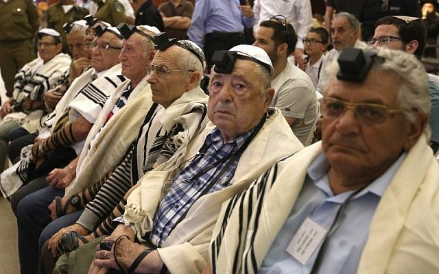Illustrative: Dozens of Jewish Holocaust survivors wear Tefilin and the Tallit prayer shawl as they participate in a group bar-mitzvah ceremony, normally done at the age of 13, on May 2, 2016, at the Western Wall in Jerusalem's Old City. (AFP PHOTO / MENAHEM KAHANA)
