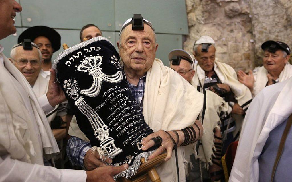 Dozens of Jewish holocaust survivors wear phylacteries and the tallit prayer shawl as they dance with the Torah after performing their bar mitzvahs, on May 2, 2016, at the Western Wall in the Jerusalem's Old City. (AFP/Menahem Kahana)