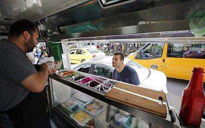 "Palestinian al-Barghuti serves food to a customer at his food truck called ""Food Train"" which he runs with his friend al-Bibi in the West Bank city of Ramallah, May 3, 2016. (AFP/ABBAS MOMANI)"