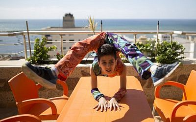 Palestinian teenager Mohammed al-Sheikh, 12, shows his skills on a table in Gaza City on April 28, 2016. / AFP PHOTO / MAHMUD HAMS