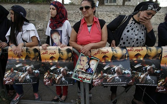 Palestinian protesters hold placards depicting portraits of Muhammed Abu Khdeir outside the Jerusalem District Court on May 3, 2016 as they await the verdict in the case of Yosef Haim Ben David, the ringleader in the killing of the Palestinian teenager last year. (AFP PHOTO / AHMAD GHARABLI)