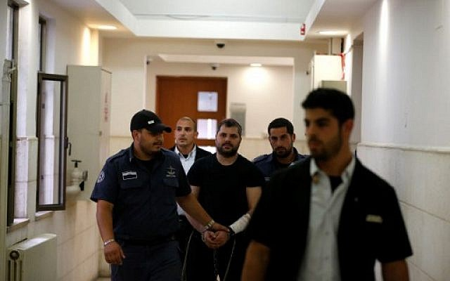 Yosef Haim Ben David (C), the ringleader in the killing of Palestinian teenager Muhammed Abu Khdeir in 2014, is escorted by Israeli policemen at the Jerusalem District Court on May 3, 2016 (AFP PHOTO / AHMAD GHARABLI)