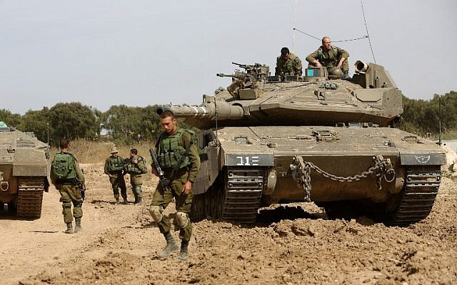 Israeli soldiers stand guard with their tank along the border between Israel and the Gaza Strip near the southern Israeli kibbutz of Nahal Oz on May 4, 2016. (AFP/Menahem Kahana)
