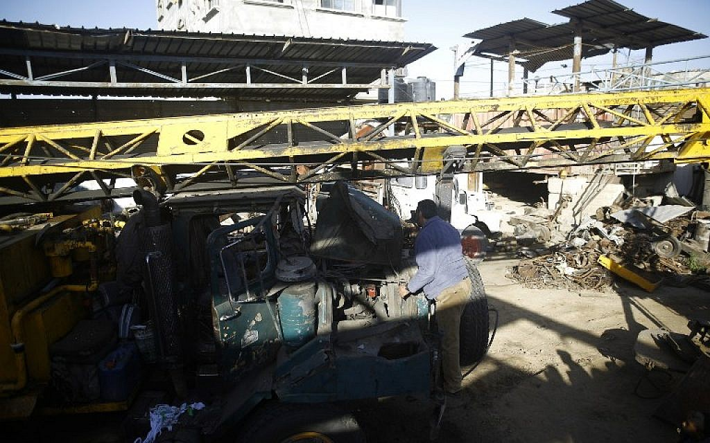 A Palestinian man inspects a damaged vehicle at his workshop after it was hit by an Israeli air strike in Gaza City, in the early hours of May 5, 2016 (AFP/MOHAMMED ABED)