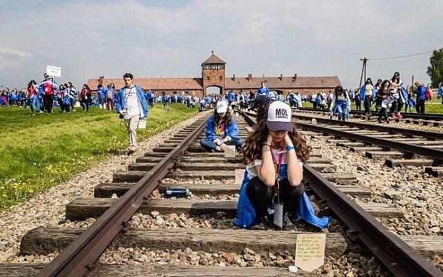 "Participants of the annual ""March of the Living"" are seen on railtracks leading to the former Auschwitz-Birkenau Nazi death camp in Brzezinka (Birkenau) near Oswiecim (Auschwitz), Poland, on May 5, 2016. (AFP PHOTO / WOJTEK RADWANSKI)"