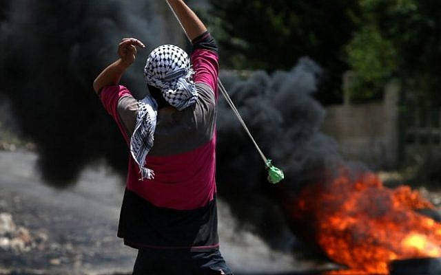 A Palestinian protester throws stones using a slingshot towards Israeli security forces during clashes on May 6, 2016.  (AFP PHOTO / JAAFAR ASHTIYEH)
