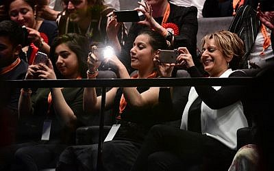 Saadiya (R), wife of newly elected London Mayor, Sadiq Khan, takes pictures as his election victory is announced at City Hall in central London on May 7, 2016. (AFP PHOTO/LEON NEAL)