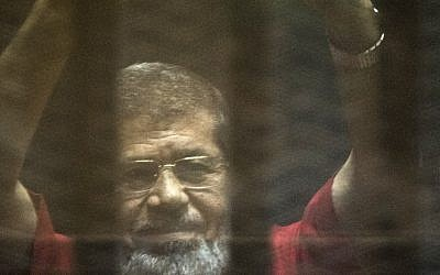Egypt's ousted Islamist president Mohammed Morsi gestures from behind the defendant's bars during his trial at the police academy in Cairo on May 7, 2016. (AFP Photo/Khaled Desouki)