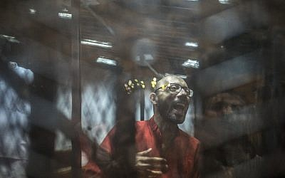 Ahmed Abdel-Aaty, the former head of Egypt's ousted Islamist president's office, wearing a red uniform, stands behind the defendant's bars during his trial at the police academy in Cairo on May 7, 2016. (AFP PHOTO/KHALED DESOUKI)