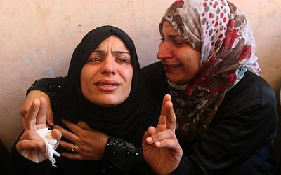 The mother of the Abu Hindi family (L) mourns during the funeral of three of her sons who died in a fire caused by a candle at the family home, at the al-Shati refugee camp in Gaza City on May 7, 2016. (AFP PHOTO/MOHAMMED ABED)