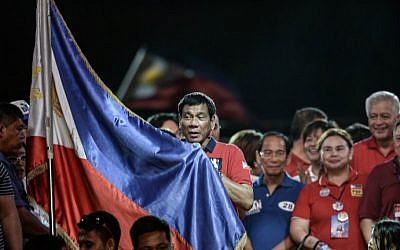 Presidential candidate and Davao Mayor Rodrigo Duterte holds his national flag as he addresses his supporters during an election campaign rally ahead of the presidential and vice presidential elections in Manila, the Philippines, on May 7, 2016. (Mohd Rasfan/AFP)