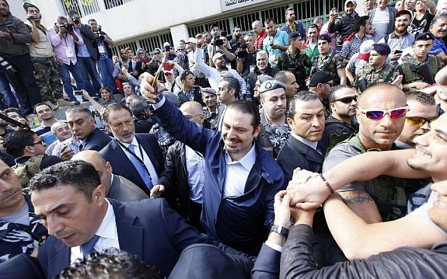Lebanese former prime minister Saad Hariri (C), whose Future Movement usually dominates elections in the capital, takes a selfie as he leaves a polling station after voting for the municipal elections on May 8, 2016 in the capital Beirut. (AFP PHOTO / ANWAR AMRO)