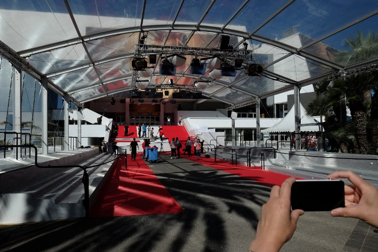 This file photo taken on May 14, 2014 shows workers setting up the red carpet at the entrance to the Palais des Festival on the opening day of the Cannes Film Festival (AFP PHOTO / ALBERTO PIZZOLI)
