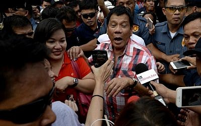 Presidential frontrunner and Davao City Mayor Rodrigo Duterte leaves the voting precint after casting his vote at Daniel Aguinaldo National High School in Davao City, on the southern island of Mindanao on May 9, 2016. (AFP PHOTO / NOEL CELIS)
