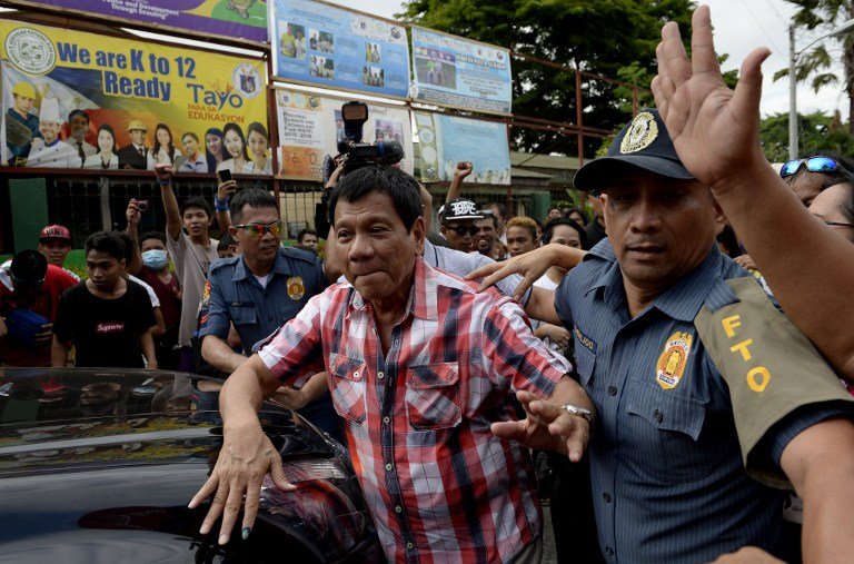 Presidential frontrunner and Davao City Mayor Rodrigo Duterte (C) leaves the voting precinct after casting his ballot at Daniel Aguinaldo National High School in Davao City, on the southern island of Mindanao on May 9, 2016. (Noel Celis/AFP)
