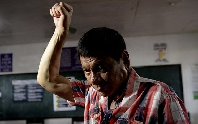 Presidential front-runner and Davao City Mayor Rodrigo Duterte gestures as he arrives at the voting precinct to cast his vote at Daniel Aguinaldo National High School in Davao City, on the southern island of Mindanao on May 9, 2016. (AFP/Noel Celis)