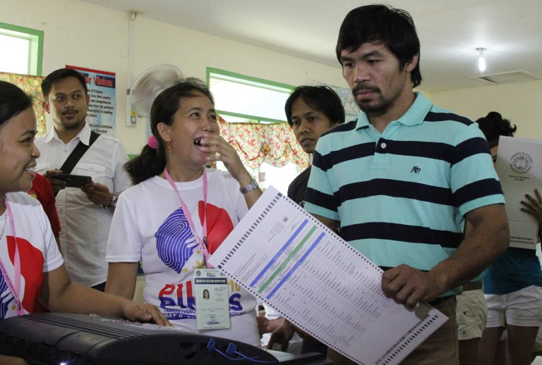 Philippine boxing icon and senatorial candidate Manny Pacquiao (R) casts his ballot at a polling station in Kiamba, Sarangani province, on the southern island of Mindanao on May 9, 2016. (AFP)