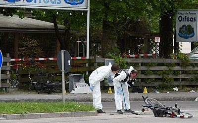 Forensic experts of the police are seen working in front of the train station in Grafing near Munich, southern Germany, where a man killed one person and wounded three others in a knife attack on May 10, 2016. (AFP PHOTO / Christof Stache)