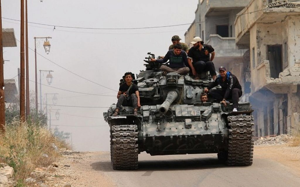 Opposition fighters drive a tank in a rebel-held area of the southern Syrian city of Daraa, during renewed clashes with regime loyalists on May 10, 2016. (AFP Photo/Mohamad Abazeed)