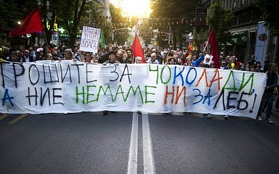 """Protesters walk behind a banner reading """"You spend for chocolate, while we don't even have enough for bread,"""" in Skopje, Macedonia on May 10, 2016. (Robert Atanasovski/AFP)"""